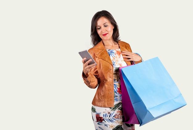 Jonge vrouw die mobiel en met sommige het winkelen zakken op een witte achtergrond bekijkt