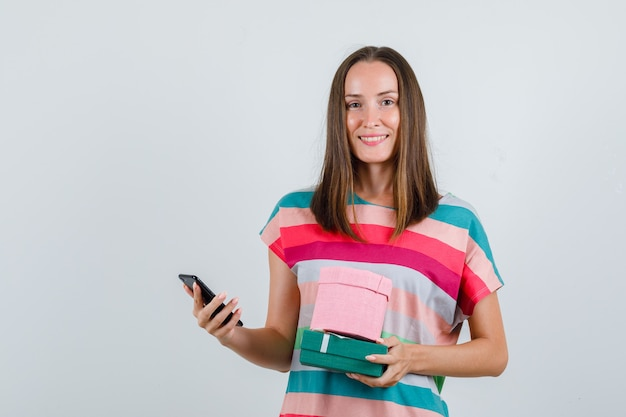 Jonge vrouw die mobiele telefoon en giftdozen in t-shirt houdt en blij, vooraanzicht kijkt.