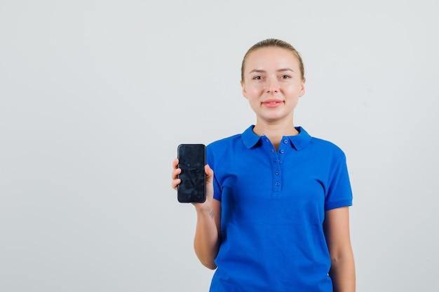 Jonge vrouw die mobiele telefoon in blauw t-shirt houdt en tevreden kijkt