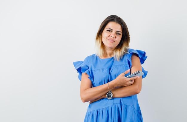 Jonge vrouw die mobiele telefoon in blauwe jurk vasthoudt en er tevreden uitziet