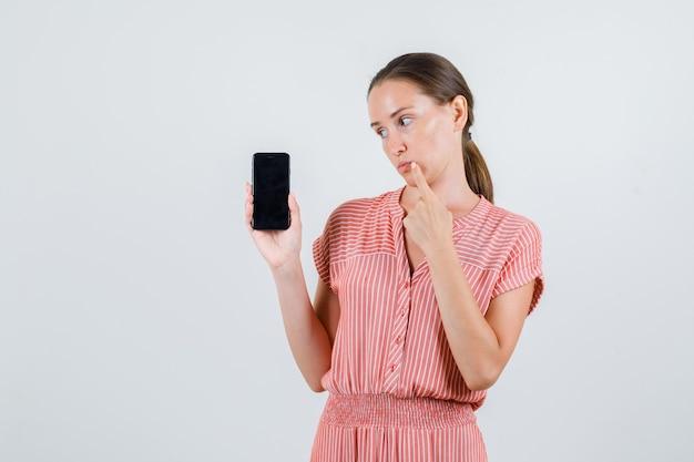 Jonge vrouw die mobiele telefoon in gestreepte kleding houdt en peinzend, vooraanzicht kijkt.