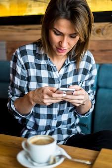 Jonge vrouw die mobiele telefoon in koffie met behulp van