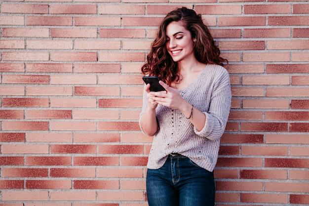 Jonge vrouw die mobiele telefoon in openlucht bij de stad met behulp van