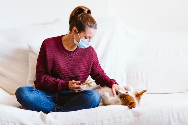 Jonge vrouw die mobiele telefoon, leuke kleine hond daarnaast gebruiken. zittend op de bank, met beschermend masker. blijf thuis concept tijdens coronavirus covid-2019