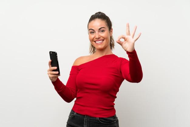 Jonge vrouw die mobiele telefoon met behulp van die ok teken met vingers toont