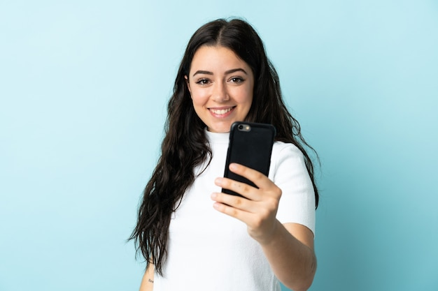 Jonge vrouw die mobiele telefoon met behulp van die op blauwe muur met gelukkige uitdrukking wordt geïsoleerd