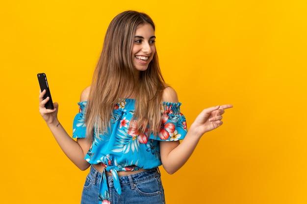 Jonge vrouw die mobiele telefoon met behulp van over geïsoleerde gele muur die naar de kant richt om een product te presenteren