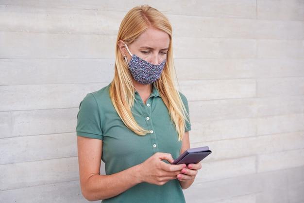 Jonge vrouw die mobiele telefoon met behulp van terwijl het dragen van gezichtsmasker tijdens coronavirusuitbraak