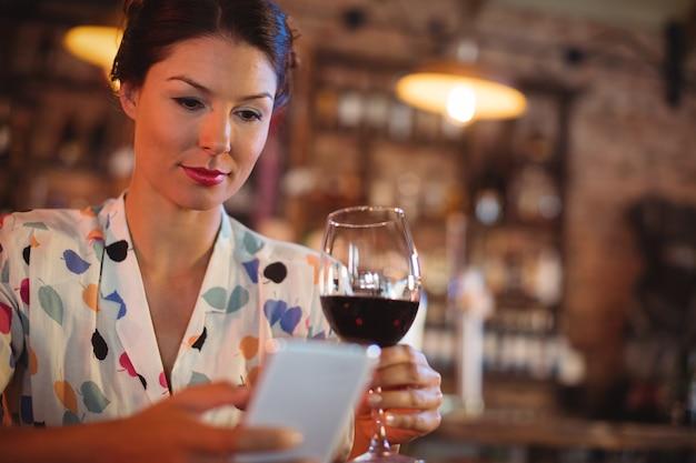 Jonge vrouw die mobiele telefoon met behulp van terwijl het hebben van wijn