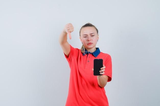 Jonge vrouw die mobiele telefoon met duim omlaag in t-shirt bekijkt en boos kijkt