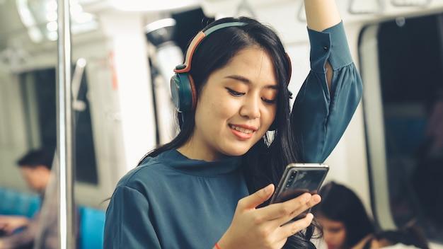 Jonge vrouw die mobiele telefoon op openbare trein met behulp van