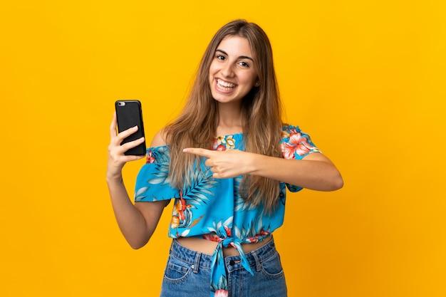 Jonge vrouw die mobiele telefoon over geïsoleerde gele muur met behulp van en het richt