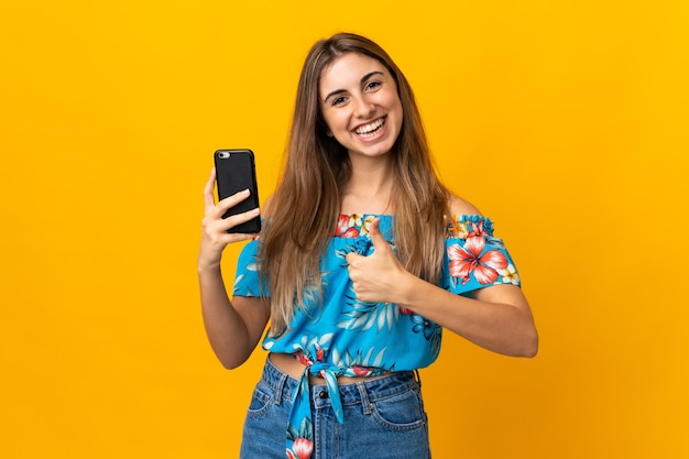 Jonge vrouw die mobiele telefoon over geïsoleerde gele muur met omhoog duimen gebruikt omdat er iets goeds is gebeurd