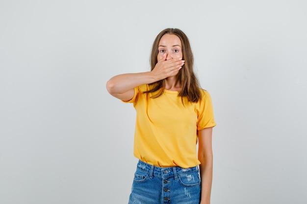 Jonge vrouw die mond bedekt met dient t-shirt, korte broek in en er stil uitziet. vooraanzicht.