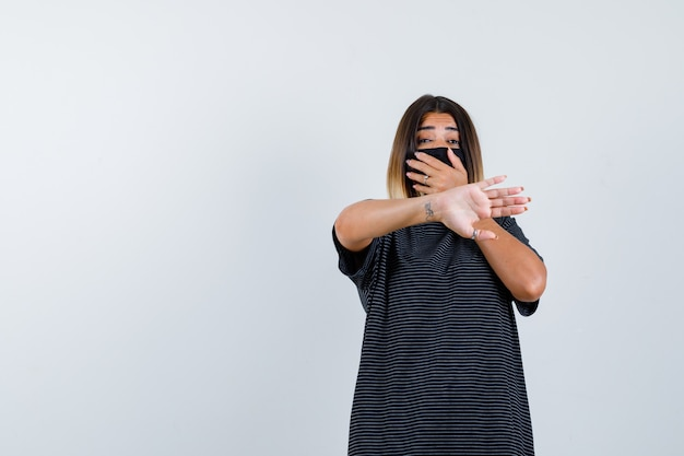 Jonge vrouw die mond bedekt met hand, stopbord in zwarte jurk, zwart masker toont en bang, vooraanzicht kijkt.