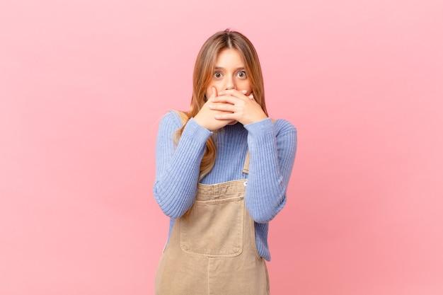 Jonge vrouw die mond bedekt met handen met een geschokt