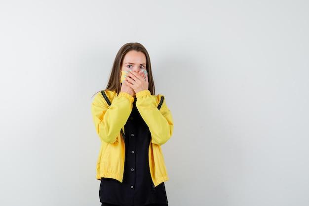 Jonge vrouw die mond bedekt met handen