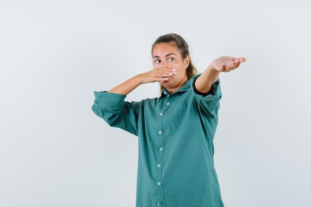 Jonge vrouw die mond bedekt terwijl het uitrekken van de hand als iets in een groene blouse ontvangt en er schattig uitziet