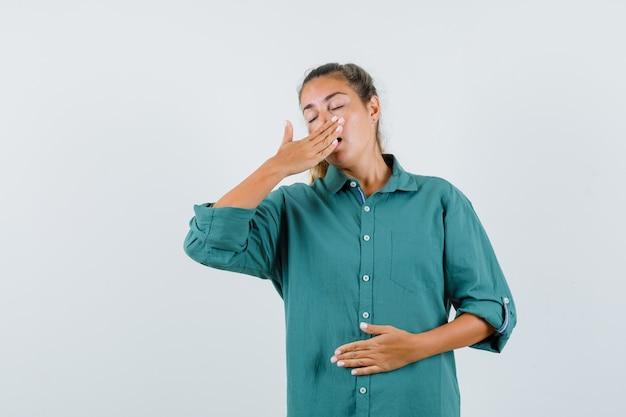 Jonge vrouw die mond behandelt met hand en in groene blouse geeuwt en slaperig kijkt