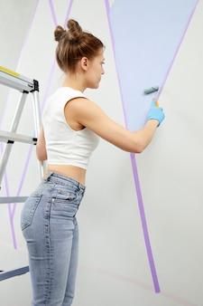Jonge vrouw die muur schildert met verfroller en plakband gebruikt terwijl ze op de ladder staat