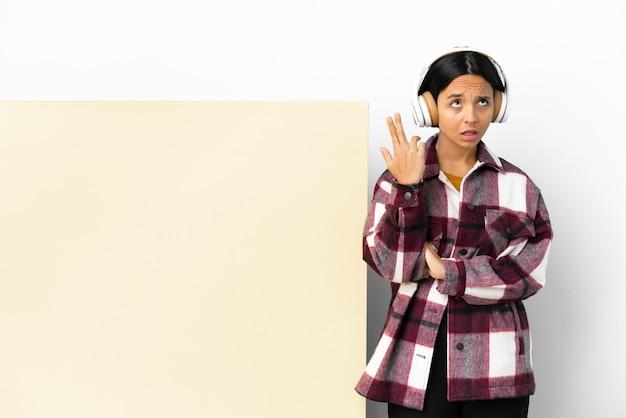 Jonge vrouw die muziek luistert met een groot leeg bordje over geïsoleerde achtergrond met problemen bij het maken van zelfmoordgebaar