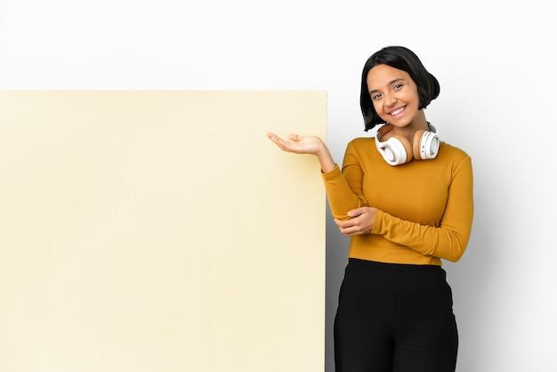 Jonge vrouw die muziek luistert met een groot leeg plakkaat geïsoleerde achtergrond die de handen naar de zijkant uitstrekt om uit te nodigen om te komen