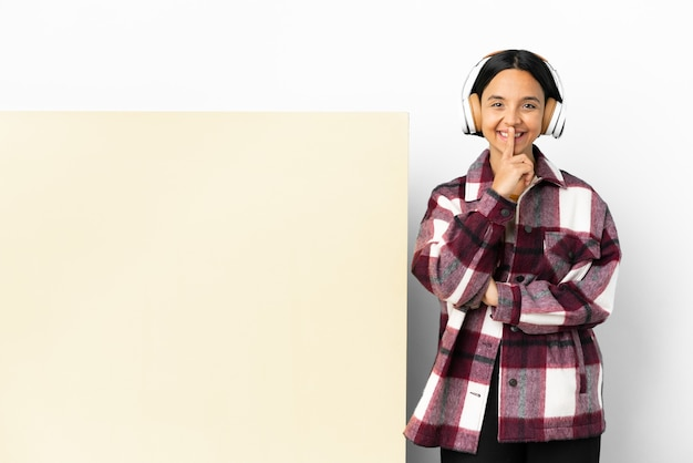 Jonge vrouw die muziek luistert met een groot leeg plakkaat geïsoleerde achtergrond met een teken van stiltegebaar dat de vinger in de mond steekt
