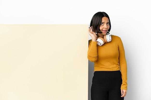 Jonge vrouw die muziek luistert met een groot leeg plakkaat over een geïsoleerde achtergrond die naar iets luistert door de hand op het oor te leggen