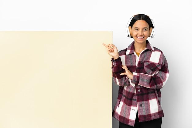 Jonge vrouw die muziek luistert met een grote lege plakkaat geïsoleerde achtergrond die naar de zijkant wijst om een product te presenteren