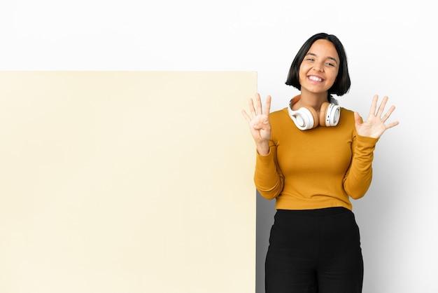 Jonge vrouw die muziek luistert met een grote lege plakkaat geïsoleerde achtergrond die negen telt met vingers