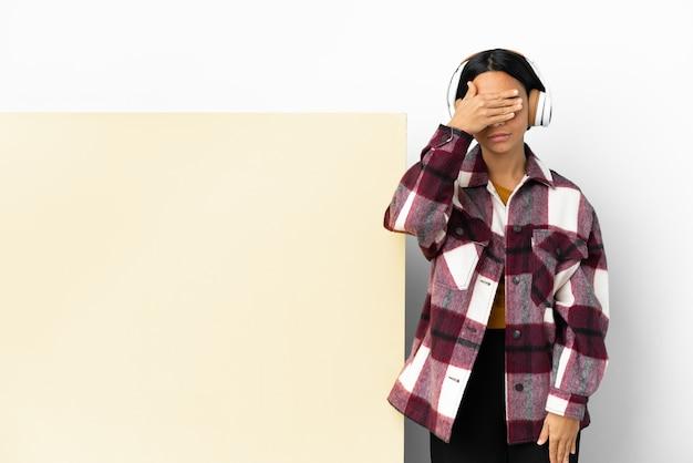 Jonge vrouw die muziek luistert met een grote lege plakkaat geïsoleerde achtergrond die ogen bedekt door handen. wil je iets niet zien