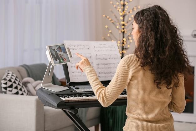 Jonge vrouw die muzieklessen thuis online geeft