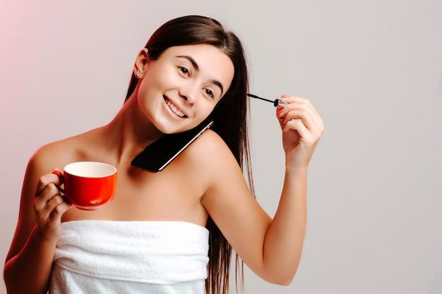 Jonge vrouw die na douche van koffie geniet en make-up in witte handdoek en naakte schouders maakt. concept van multitasking. het meisje drinkt koffie en zet een mascara op.