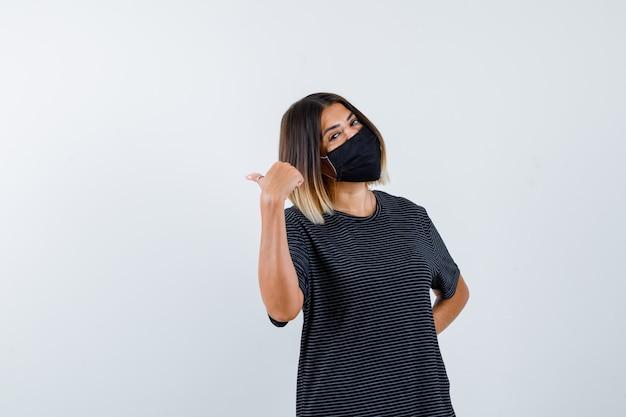 Jonge vrouw die naar achteren wijst, hand achter de taille houdt in zwarte jurk, zwart masker en er gelukkig uitziet. vooraanzicht.