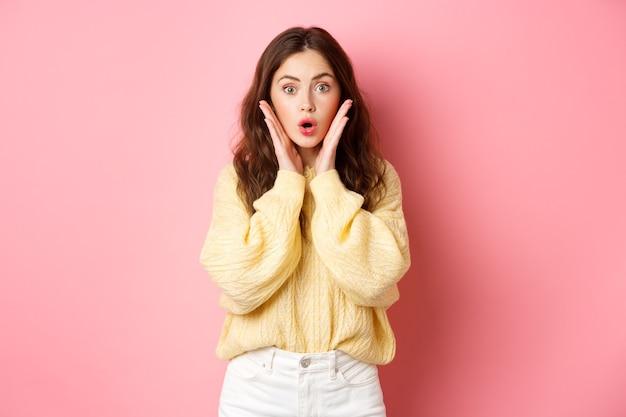 Jonge vrouw die naar adem snakt en wauw zegt, verbaasd naar de camera kijkt, promotie bekijkt, naar promo-aanbieding staart, staande tegen de roze muur.