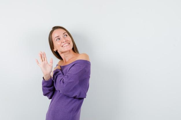 Jonge vrouw die naar boven kijkt en zwaait hand in violet overhemd en op zoek vrolijk, vooraanzicht.