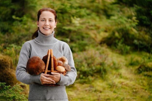 Jonge vrouw die naar de camera kijkt, houdt eetbare paddenstoelen vast die in een mand zijn verzameld