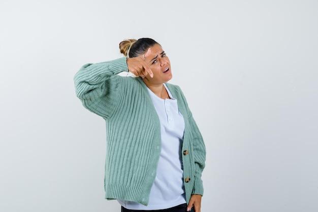 Jonge vrouw die naar de camera wijst met wijsvinger in wit t-shirt en mintgroen vest en er optimistisch uitziet
