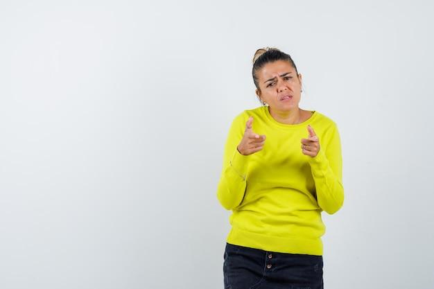 Jonge vrouw die naar de camera wijst met wijsvingers in gele trui en zwarte broek en er gehaast uitziet