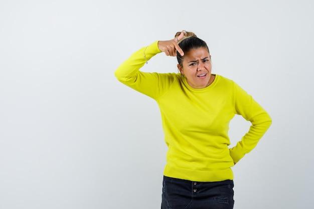 Jonge vrouw die naar de camera wijst terwijl ze de hand achter de taille houdt in een gele trui en zwarte broek en boos kijkt