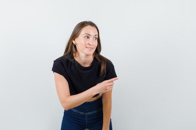 Jonge vrouw die naar de kant in zwarte blouse richt en tevreden kijkt.