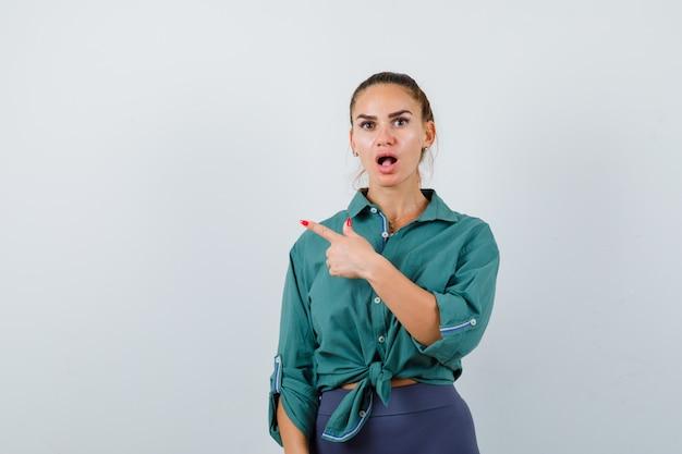 Jonge vrouw die naar de linkerbovenhoek wijst in een groen shirt en er geschokt uitziet. vooraanzicht.