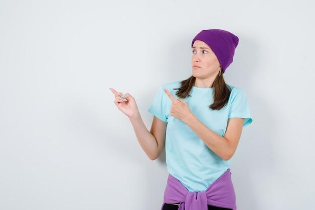 Jonge vrouw die naar de linkerbovenhoek wijst in t-shirt, muts en er bang uitziet. vooraanzicht.