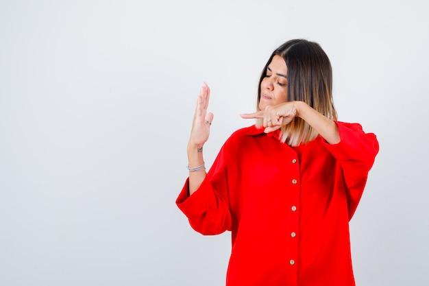 Jonge vrouw die naar de palm in een rood oversized shirt wijst en er zelfverzekerd uitziet, vooraanzicht.