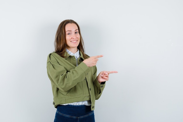 Jonge vrouw die naar de rechterkant wijst in shirt, jas en er optimistisch uitziet, vooraanzicht.
