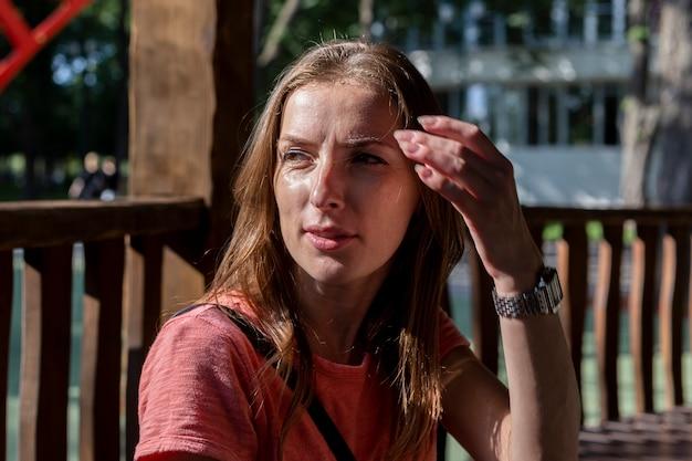 Jonge vrouw die naar de zijkant kijkt, maakt haar op een zonnige dag recht.