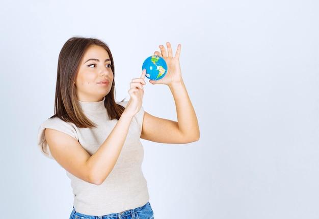 Jonge vrouw die naar een bol van de aarde kijkt
