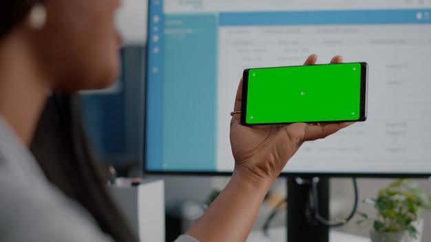 Jonge vrouw die naar een geïsoleerd scherm kijkt met een online videocall-conferentievergadering met behulp van een chroma key-telefoon met een groen scherm die aan een bureau in de woonkamer zit