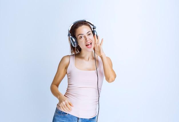 Jonge vrouw die naar een koptelefoon luistert en fluistert