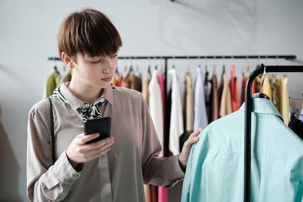 Jonge vrouw die naar een nieuw shirt op het rek kijkt en haar mobiele telefoon gebruikt tijdens het winkelen in de winkel